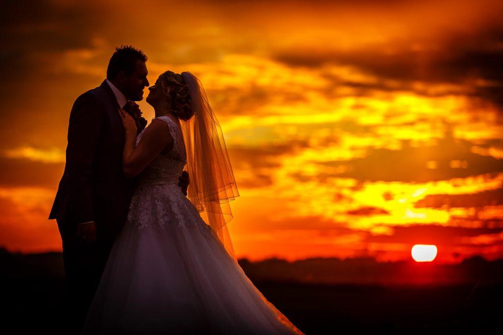 Eben die letzten Sonnenstrahlen einfangen - Hochzeitspaar bei Sonnenuntergang
